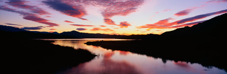 Wall Mural - This is Lake Casitas at sunrise. There is a pinkish glow from the sun reflected in the lake.