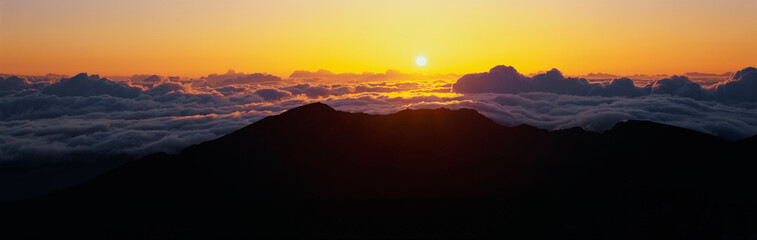 Wall Mural - This is sunrise from Haleakala Volcano Summit located at Haleakala National Park. These are the cloud formations over the top of the volcano.