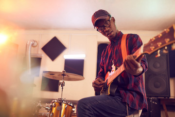Low angle portrait of contemporary African-American man playing guitar and looking at camera during rehearsal or concert with music band in studio, copy space Fotomurales