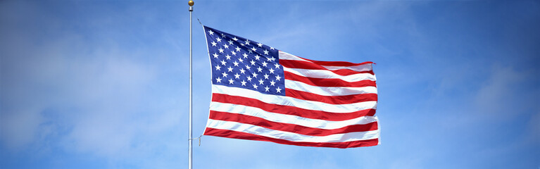 This is a shot of an American flag on a flagpole, waving in the wind against a blue sky.
