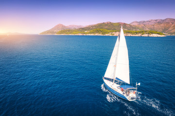 Aerial view of beautiful white sailboat in blue sea at bright sunny summer evening. Adriatic sea in...
