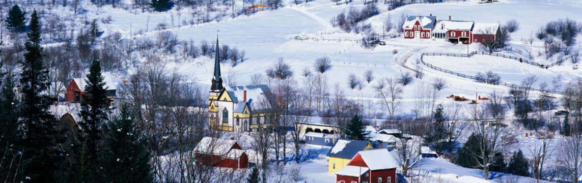 This is an aerial view of East Orange. There is a black steepled church and a small village. The village is covered in snow with houses spread across the field.