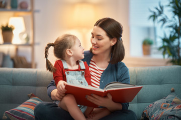 mother reading a book to daughter