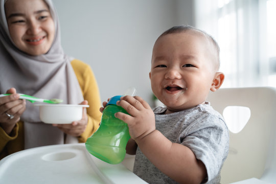 cute asian baby boy smiling to camera while eating sitting on high chair