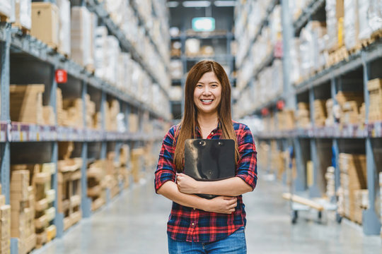 Portrait of Asian woman warehouse worker standing and holding the clipboard for checking goods stock in warehouse, shopping and self service, business furniture and storehouse industry concept