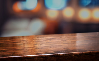 nightclub background.Empty diagonal brown wooden table with blur bar restaurant bokeh lights,banner mockup template for display of product