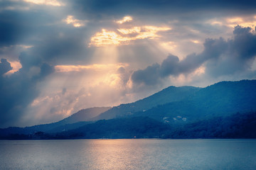 Fototapete - Bright beautiful dawn over the mountains, view from the sea, thick clouds and the sun
