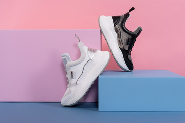 white and black female sneakers of the same model stand on a pink, blue stand from the studio. Promotional photo