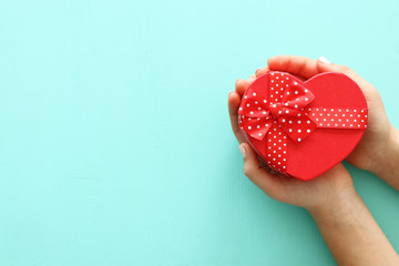 Valentine's, father's and mother's day background. Little child holding red heart present box. Top view