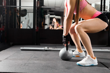slim woman wearing pink and black professional sportswear exercising with a kettlebell at the gym. fitness and workout concept. close up photo of legs