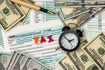 American dollars with clock over individual tax form