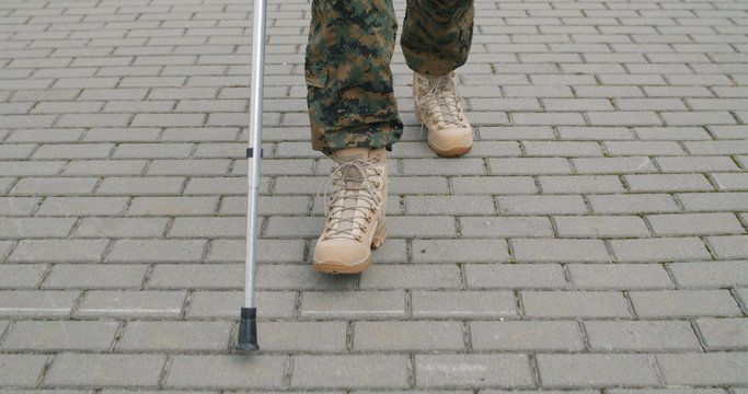 Front view of wounded soldier with crutch.