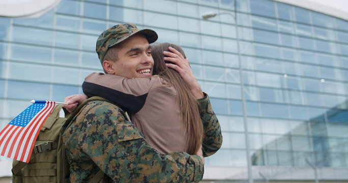 Soldier man embracing his lovely wife.