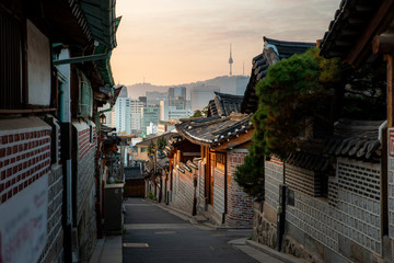 Stores photo Seoul Traditional Korean style architecture at Bukchon Hanok Village with N Seoul Tower in background in Seoul, South Korea. Asian tourism, history building, or tradition culture and travel concept