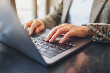 Closeup image of a woman working and typing on laptop computer on the table