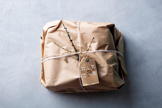 Gift box wrapped in craft paper with a rustic twine and decorations. Grey background. Top view. Copy space.