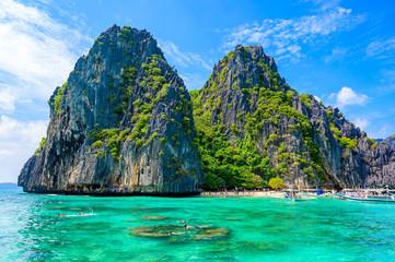 Tropical Shimizu Island and paradise beach, El Nido, Palawan, Philippines. Tour A Route. Coral reef and sharp limestone cliffs.