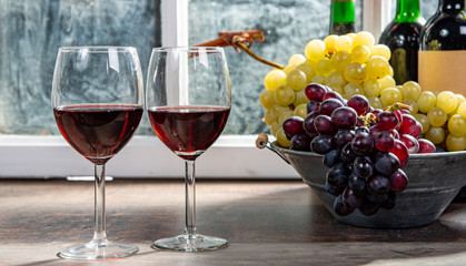 Foto auf Leinwand Alkohol two wineglasses, red and white grapes with bottles of red wine
