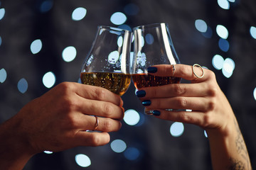 Foto op Canvas Alcohol A couple makes a toast with two glasses of whiskey on festive background