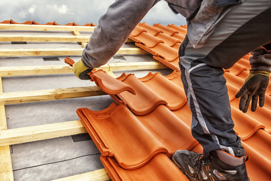 Roofer at work, installing clay roof tiles, Germany