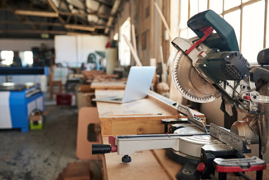 Mitre saw and laptop on workbenches in a woodworking shop