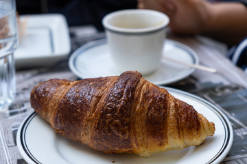 A well-done croissant on white dish in close up view. Blur cup on a saucer background.