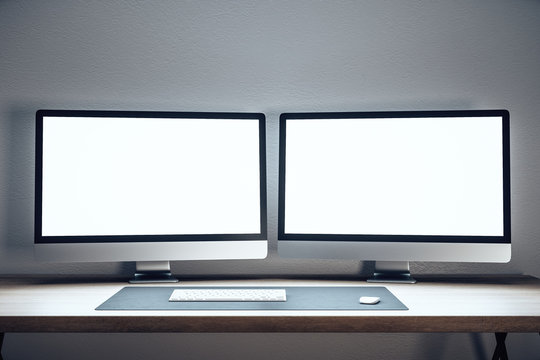 Designer desktop with two empty computer monitor
