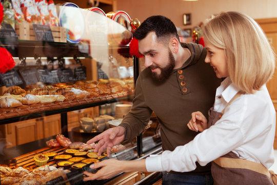 Female baker enjoying working at her bakery, helping her customer choose dessert from the display