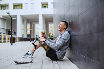 Fotomurales - Young attractive caucasian sportsman with artificial leg sitting on ground, leaning on wall and eating fresh apple.
