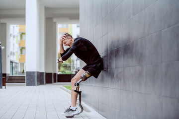 Fotomurales - Upset handsome caucasian sportsman with artificial leg leaning on the wall, holding head and looking at wristwatch.
