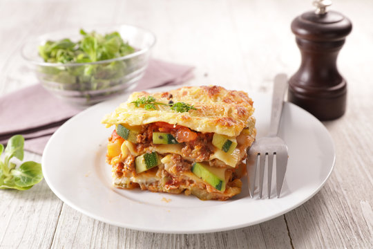 plate of lasagna with minced beef, tomato sauce and vegetable