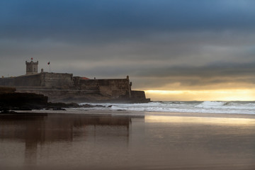 View of the Carcavelos Beach with the Sao Juliao da Barra Fort on the background at sunrise, in Portugal.