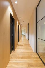 Interior of a long hotel corridor, doorway