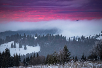Dramatic pink sunrise in winter frozen mountains.