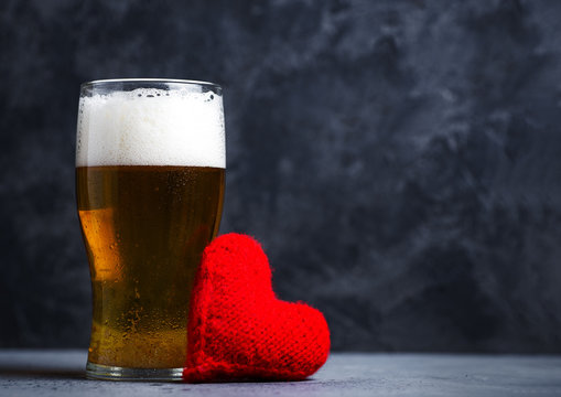 A glass of light beer for Valentine's day and a red heart copy space