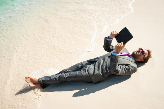 Relaxed businessman lying in a wet suit using his tablet computer on the shore of a tropical beach