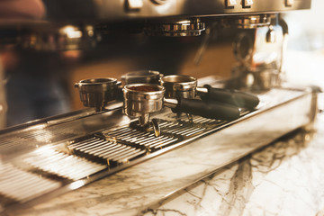 picture of two coffee holders one with ground coffee near professional coffee machine close up