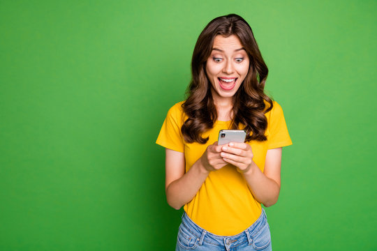 Portrait of her she nice attractive lovely charming girlish cheerful cheery wavy-haired girl having fun using app 5g device isolated over bright vivid shine vibrant green color background
