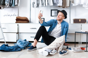 Stylish young man taking selfie in dressing room Wall mural