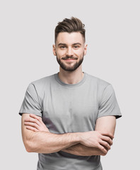 Portrait of handsome smiling young man with folded arms. Smiling joyful cheerful men with crossed hands studio shot. Isolated on gray background