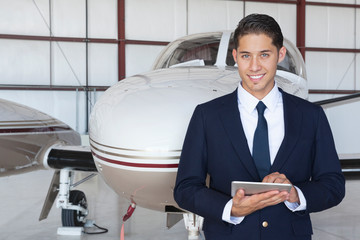 Portrait of handsome young pilot using tablet PC in front of airplane Wall mural