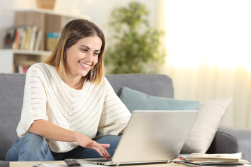 Happy woman checking laptop online content at home