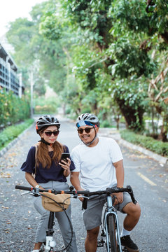 asian couple who wore helmets with cell phones seemed happy to ride bicycles together on trips in the park