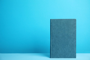 Hardcover book on blue background. Space for design