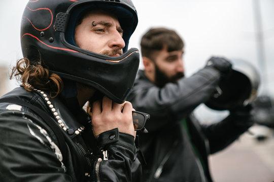 Photo of bearded brutal men bikers wearing helmets looking forward