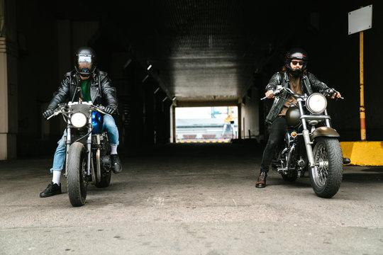 Photo of bearded brutal men bikers on bikes wearing helmets