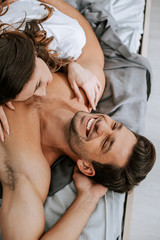 top view of happy young woman lying on bed with muscular boyfriend