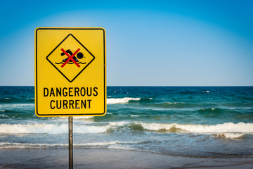 Dangerous current warning sign for swimmers at beach