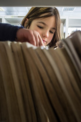 Young girl selecting books from library bookshelf