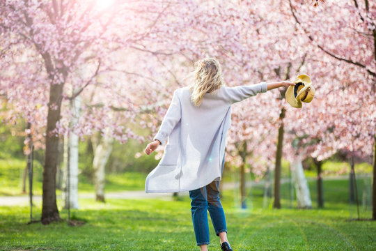 Young woman enjoying the nature in spring. Dancing, running and whirling in beautiful park with cherry trees in bloom. Happiness concept
